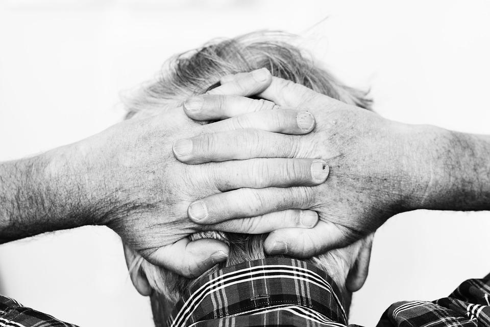 Руки старого человека на затылке