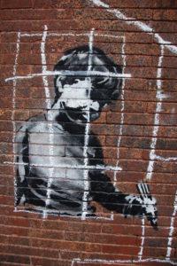 Рисунок на стене (Банкси?): мальчик за решёткой.