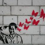 Графити. Человек стреляет себе в голову, вылетают красные бабочки.